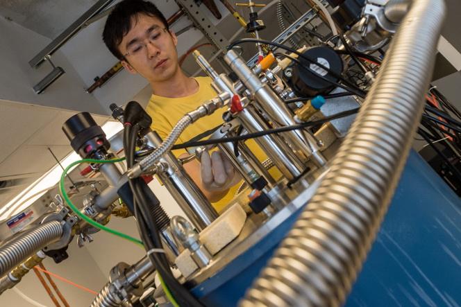 El investigador de la Universidad de Rice, Xinwei Li, con el espectrómetro de terahercios que luego utilizó para medir el entrelazamiento cuántico de los electrones que fluyen en el interior del metal raro. Foto: Jeff Fitlow/Rice University.